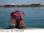 Купить «Женщина с мужчиной сидят и смотрят на море под зонтиком на набережной города Ялты, Республика Крым», фото № 25790094, снято 7 мая 2016 г. (c) Николай Винокуров / Фотобанк Лори