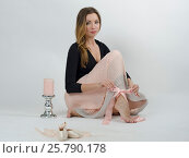 Beautiful young elegant woman sitting with pink items such as candle, ribbon and shoes for ballet against white background. Стоковое фото, фотограф Мария Сидельникова / Фотобанк Лори