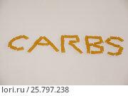 Conchiglie pasta arrange in shape of carbs text. Стоковое фото, агентство Wavebreak Media / Фотобанк Лори