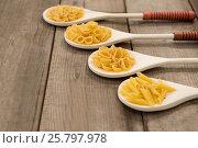 Купить «Spoons filled with varieties of pasta», фото № 25797978, снято 13 октября 2016 г. (c) Wavebreak Media / Фотобанк Лори