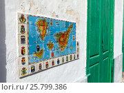 Купить «Фреска на фасаде дома из плитки с картой Канарских островов и гербами основных крупных городов. Гарачико, Тенерифе, Испания», фото № 25799386, снято 8 января 2016 г. (c) Кекяляйнен Андрей / Фотобанк Лори