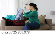 Купить «woman packing clothes to travel bag at home», видеоролик № 25803978, снято 19 января 2017 г. (c) Syda Productions / Фотобанк Лори