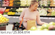 Купить «pregnant woman with basket buying pears at grocery», видеоролик № 25804014, снято 8 февраля 2017 г. (c) Syda Productions / Фотобанк Лори