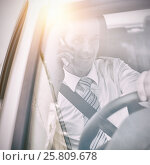 Купить «Man driving a car and using his phone», фото № 25809678, снято 16 июня 2019 г. (c) Wavebreak Media / Фотобанк Лори