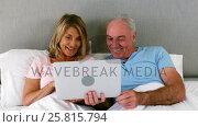 Smiling couple lying on bed and using laptop. Стоковое видео, агентство Wavebreak Media / Фотобанк Лори