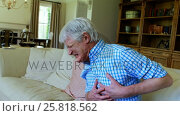 Купить «Senior man suffering from chest pain in living room», видеоролик № 25818562, снято 16 июля 2019 г. (c) Wavebreak Media / Фотобанк Лори