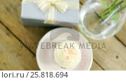 Gift box and flower vase with cupcake in plate on wooden plank. Стоковое видео, агентство Wavebreak Media / Фотобанк Лори