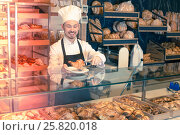 Купить «Experienced male pastry maker demonstrating croissant», фото № 25820018, снято 26 января 2017 г. (c) Яков Филимонов / Фотобанк Лори