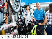 Купить «father with son and female seller in bike store», фото № 25820134, снято 27 сентября 2016 г. (c) Яков Филимонов / Фотобанк Лори