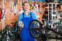 seller with bike wheel in hand in store, фото № 25820146, снято 27 сентября 2016 г. (c) Яков Филимонов / Фотобанк Лори