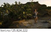 Купить «Cheering young woman backpacker at sunrise seaside mountain peak», видеоролик № 25824222, снято 18 марта 2017 г. (c) Valentyn Kondratiuk / Фотобанк Лори