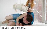 Young woman striking her boyfriend with plush toy. Стоковое видео, видеограф Илья Насакин / Фотобанк Лори