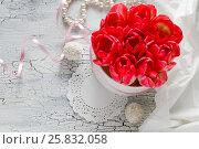 Букет красных тюльпанов в коробке, жемчужные бусы и сладости на белом фактурном фоне. Стоковое фото, фотограф Kroshanya / Фотобанк Лори
