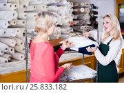 Купить «Cheerful seller offering fabrics to aged woman», фото № 25833182, снято 15 февраля 2017 г. (c) Яков Филимонов / Фотобанк Лори