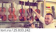 Купить «Male musician selecting classical violin», фото № 25833242, снято 16 октября 2018 г. (c) Яков Филимонов / Фотобанк Лори