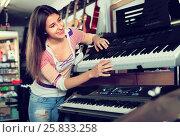 Купить «Girl choosing synthesizer in store», фото № 25833258, снято 19 августа 2018 г. (c) Яков Филимонов / Фотобанк Лори