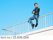 Купить «Young man in denim clothes sits with his arms crossed on his chest, on the metal railing of the building roof», фото № 25836054, снято 12 июня 2015 г. (c) Losevsky Pavel / Фотобанк Лори