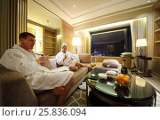 Купить «Man and woman in bathrobes drink wine on couch in hotel room», фото № 25836094, снято 5 ноября 2015 г. (c) Losevsky Pavel / Фотобанк Лори