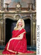 Купить «Blonde woman with decoration on head in red dress sits at fireplace in room», фото № 25836154, снято 17 сентября 2015 г. (c) Losevsky Pavel / Фотобанк Лори