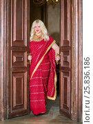 Купить «Blonde woman in red dress stands in doorway holding doors handles», фото № 25836186, снято 17 сентября 2015 г. (c) Losevsky Pavel / Фотобанк Лори