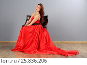 Купить «Pretty woman with make up in red dress poses on chair in studio», фото № 25836206, снято 26 апреля 2015 г. (c) Losevsky Pavel / Фотобанк Лори