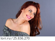 Купить «Pretty young woman with pink lips and long hair smiles and looks away in grey studio», фото № 25836270, снято 26 апреля 2015 г. (c) Losevsky Pavel / Фотобанк Лори