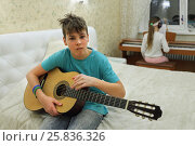 Купить «Two people in bedroom: boy holding guitar girl playing on synthesizer in background», фото № 25836326, снято 9 марта 2015 г. (c) Losevsky Pavel / Фотобанк Лори