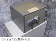 Купить «Small metal safe with key and combination lock on box in corner of room», фото № 25836430, снято 11 марта 2015 г. (c) Losevsky Pavel / Фотобанк Лори