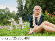 Young blond woman sits on grass in summer park, two husky dogs sit behind her, фото № 25836498, снято 23 июля 2015 г. (c) Losevsky Pavel / Фотобанк Лори
