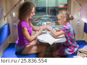 Купить «Mother and daughter eat, sitting in bench at table near window of moving speed train», фото № 25836554, снято 4 августа 2014 г. (c) Losevsky Pavel / Фотобанк Лори