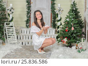 Купить «Full portrait of young woman sitting on squatting in courtyard of fake home and holds in her hands snow, smiling and look at us. Christmas interior studio», фото № 25836586, снято 14 декабря 2014 г. (c) Losevsky Pavel / Фотобанк Лори
