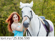 Купить «Young smiling red-haired woman holds white horse by bridle in park», фото № 25836590, снято 20 сентября 2015 г. (c) Losevsky Pavel / Фотобанк Лори