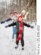 Купить «Happy family of four stands on skates on ice pathway in winter park spreading arms to sides», фото № 25836602, снято 25 января 2015 г. (c) Losevsky Pavel / Фотобанк Лори