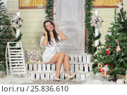 Купить «Full portrait of young woman sitting on threshold of fake home and listening music in headphone, smiling and look at us. Christmas interior studio», фото № 25836610, снято 14 декабря 2014 г. (c) Losevsky Pavel / Фотобанк Лори