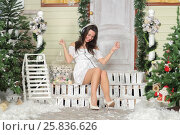 Купить «Full portrait of young woman sitting on threshold of fake home and listening music in headphone and dance sitting, head down, smile. Christmas interior studio», фото № 25836626, снято 14 декабря 2014 г. (c) Losevsky Pavel / Фотобанк Лори