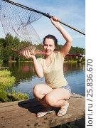 Купить «Smiling woman holds caught carp in landing net at pond bank», фото № 25836670, снято 25 июля 2015 г. (c) Losevsky Pavel / Фотобанк Лори