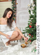 Купить «Full portrait of young woman sitting on squatting in courtyard of fake home and picks up toy from snow. Christmas interior studio», фото № 25836674, снято 14 декабря 2014 г. (c) Losevsky Pavel / Фотобанк Лори