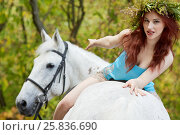 Купить «Young smiling red-haired woman with floral wreath on head sits backwards on horseback in park», фото № 25836690, снято 20 сентября 2015 г. (c) Losevsky Pavel / Фотобанк Лори