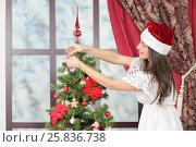 Купить «Half-length portrait of woman near Christmas tree. Girl in white dress and Santa hat dresses up Christmas tree.», фото № 25836738, снято 14 декабря 2014 г. (c) Losevsky Pavel / Фотобанк Лори
