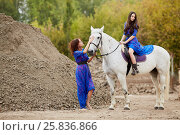 Купить «Woman holds by bridle white horse on which her daughter sits in park near ground pile», фото № 25836866, снято 20 сентября 2015 г. (c) Losevsky Pavel / Фотобанк Лори