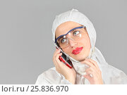 Купить «Headshot of woman in white protective suit of synthetic paper, glasses and respiritory half mask, talking on phone, on gray background», фото № 25836970, снято 14 декабря 2014 г. (c) Losevsky Pavel / Фотобанк Лори