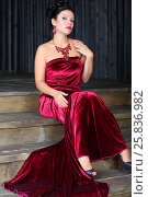 Pretty woman in red long velvet dress sits on stairs in studio. Стоковое фото, фотограф Losevsky Pavel / Фотобанк Лори