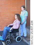 Купить «Nurse and patient in wheelchair in front of main entrance in medical facility, focus on nurse», фото № 25837234, снято 19 марта 2015 г. (c) Losevsky Pavel / Фотобанк Лори