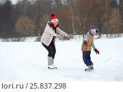 Купить «Happy mother catches her cute little son skating on ice in winter day», фото № 25837298, снято 31 января 2015 г. (c) Losevsky Pavel / Фотобанк Лори