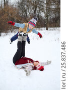 Купить «Happy woman lies on her back and holds little son on feet in snow», фото № 25837486, снято 31 января 2015 г. (c) Losevsky Pavel / Фотобанк Лори