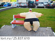 Купить «Boy in inflatable sumo wrestler suit sitting on bench on territory near house», фото № 25837610, снято 24 июня 2014 г. (c) Losevsky Pavel / Фотобанк Лори