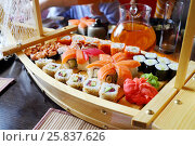 Купить «Close up of wooden boat-plate with variety of sushi on table», фото № 25837626, снято 5 мая 2015 г. (c) Losevsky Pavel / Фотобанк Лори