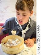 Купить «Boy eating Chinese dumplings from a wooden plate», фото № 25837666, снято 8 сентября 2014 г. (c) Losevsky Pavel / Фотобанк Лори