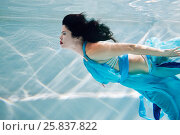 Купить «Young black-haired woman in blue dress swims underwater with her eyes close», фото № 25837822, снято 14 мая 2016 г. (c) Losevsky Pavel / Фотобанк Лори