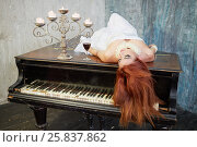 Купить «Woman in white dress lies with her eyes closed on old black grand piano lid with candles and glass of red wine», фото № 25837862, снято 12 февраля 2015 г. (c) Losevsky Pavel / Фотобанк Лори